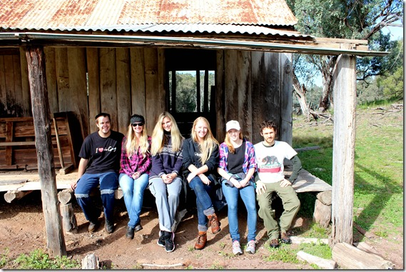 IYL Volunteers sit on the verandah of an old log cabin on the property